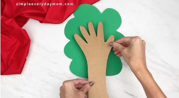 hands gluing handprint onto green tree background