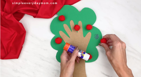 hands gluing red pom poms onto paper tree