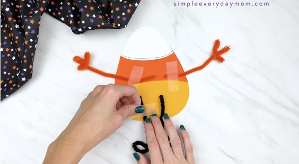 hands taping pipe cleaner legs to the back of paper candy corn craft