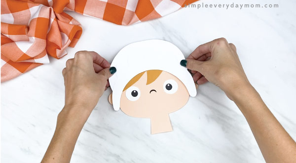 hands gluing bonnet to girl pilgrim craft