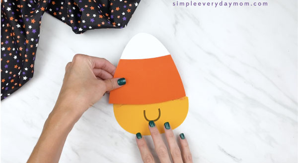 hands gluing paper candy corn craft body together