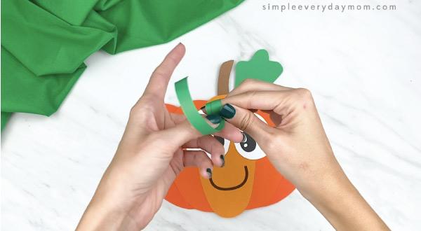 hands twisting green paper around finger
