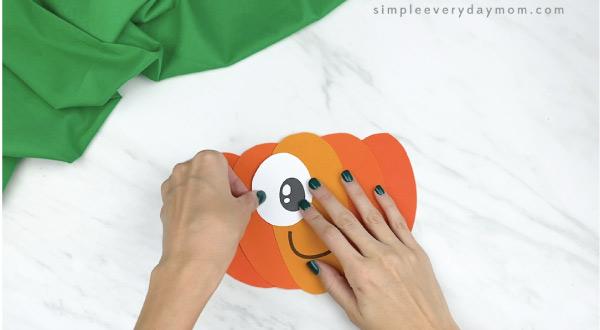 hands gluing eyes to paper pumpkin craft