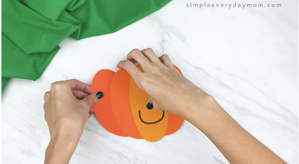 hands gluing paper pumpkin pieces together