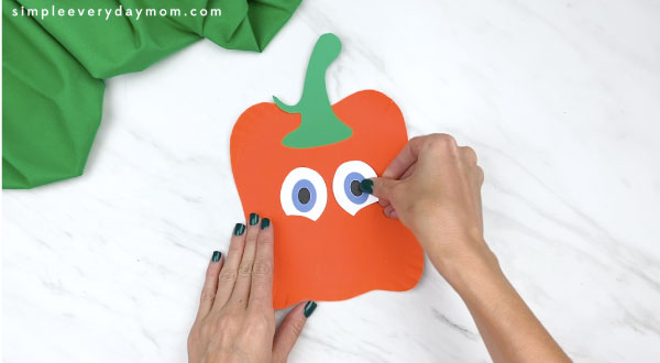 Hands gluing eyes onto paper plate spookley craft