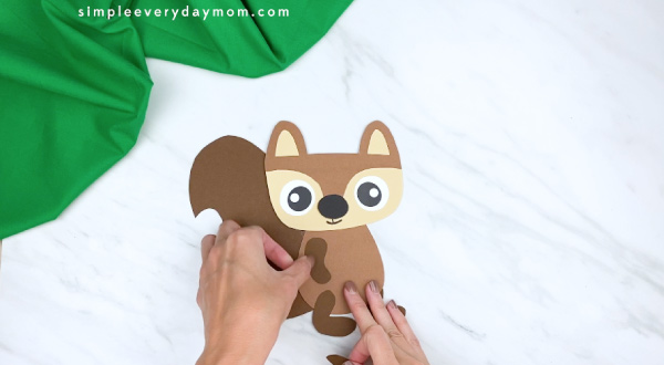 hands gluing paper squirrel arms onto craft
