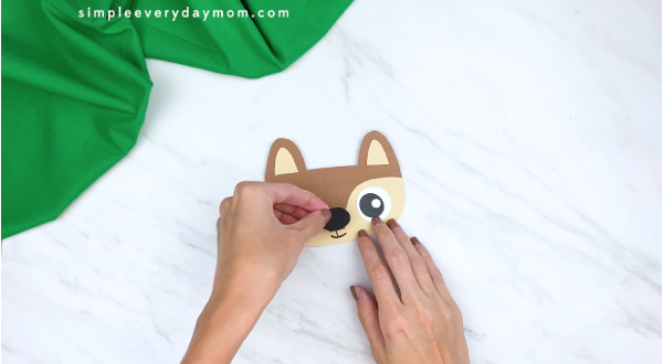 hands gluing nose onto paper squirrel head