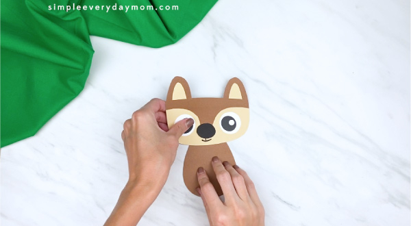 hands gluing squirrel head to body