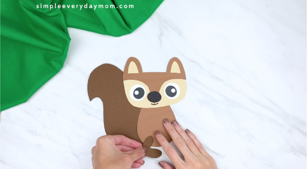 hands gluing paper squirrel legs to body