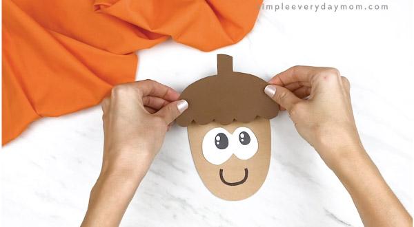 hands gluing acorn cap onto paper acorn