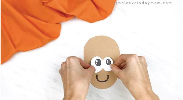 hands gluing eyes onto paper acorn craft