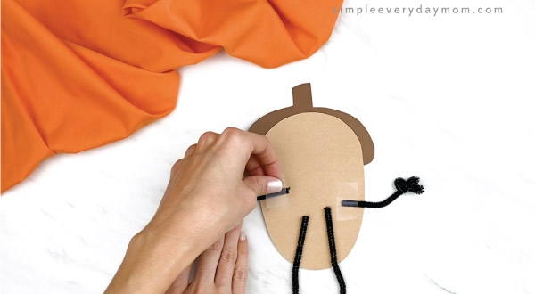 hands taping pipe cleaner arms and legs onto acorn craft