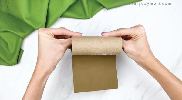 hands rolling paper hedgehog around toilet paper roll