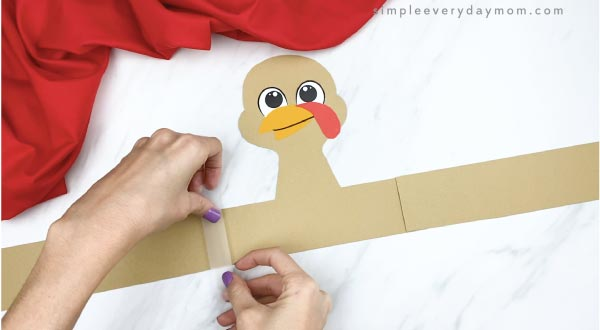 hands taping headband turkey craft together
