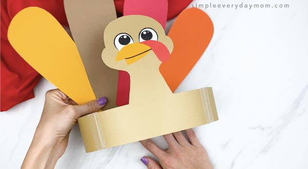 hands taping feathers into headband turkey craft