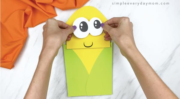 hands gluing eyes to paper bag corn craft