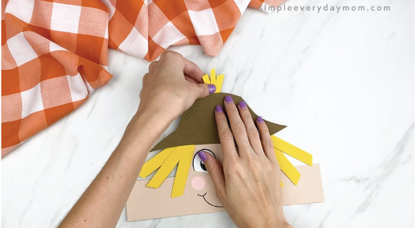 hands gluing top hair pieces onto scarecrow headband