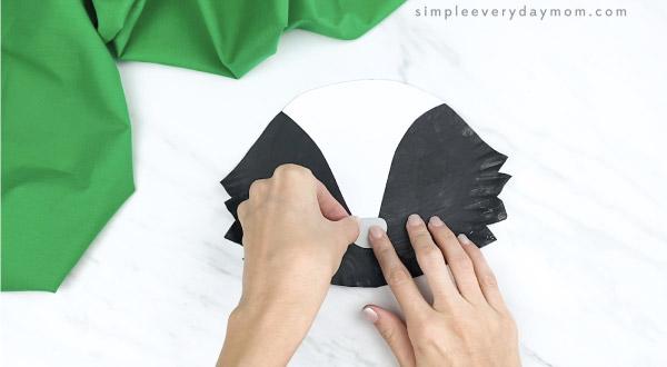 hands gluing nose onto paper plate skunk