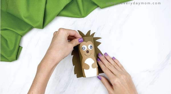 hands gluing toilet paper roll hedgehog to paper quills