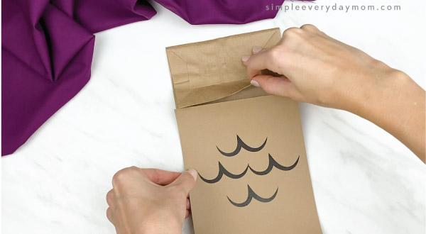 hands gluing owl body onto paper bag