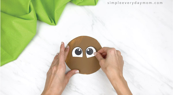 hands gluing eyes onto brown paper plate