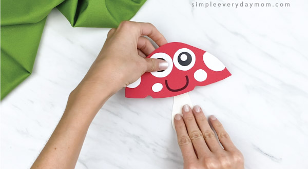 hands gluing stalk to bottom of paper mushroom craft