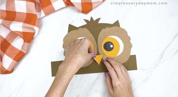 hands gluing beak to headband owl craft
