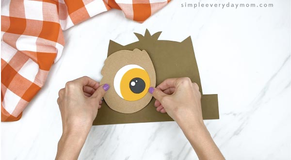 hands gluing paper owl eye to headband base