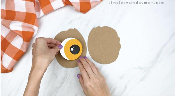 hands gluing paper owl eye to feather outline