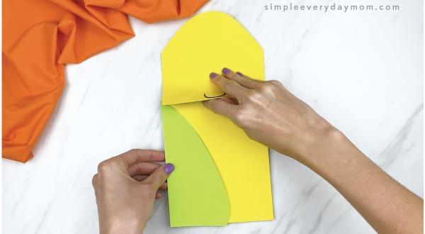 hands gluing paper husk to corn puppet craft