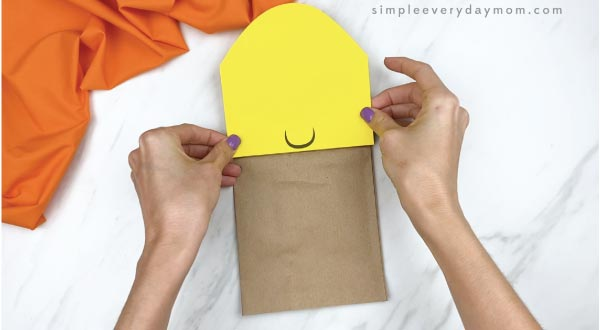 hands gluing head on paper bag corn craft