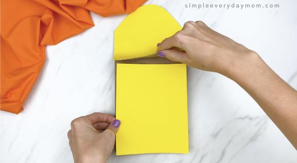 hands gluing yellow paper on paper bag corn craft