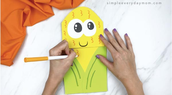 hands drawing on paper bag corn craft with marker