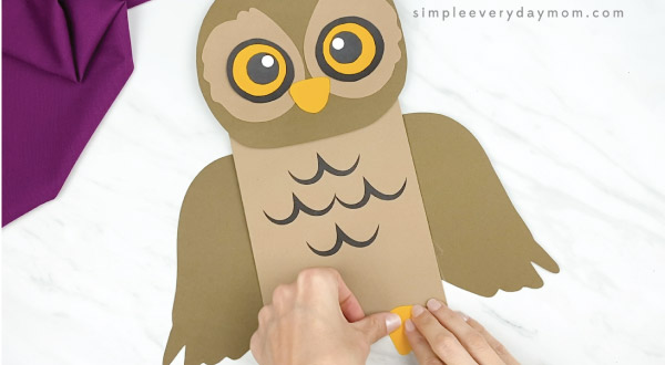 hands gluing feet to paper bag owl craft