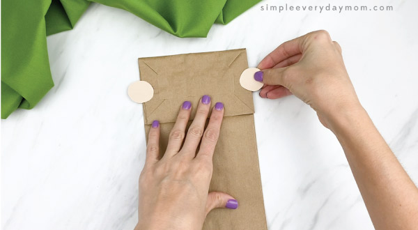 hands gluing ears to paper bag pilgrim craft