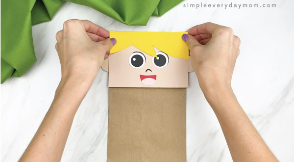 hands gluing hair to paper bag pilgrim craft
