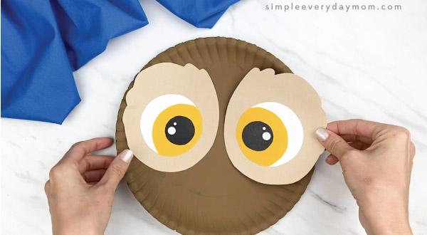 hands gluing eyes to paper plate