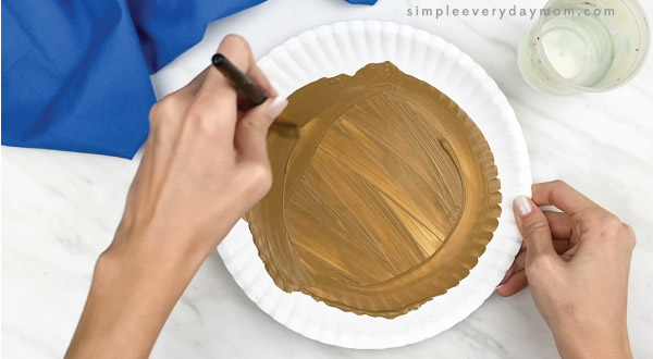hands painting paper plate brown