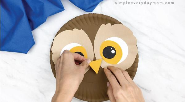 hands gluing beak to paper plate owl craft
