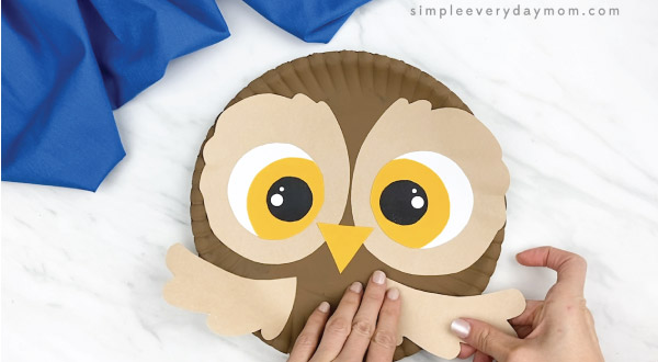 hands gluing wings to paper plate owl craft