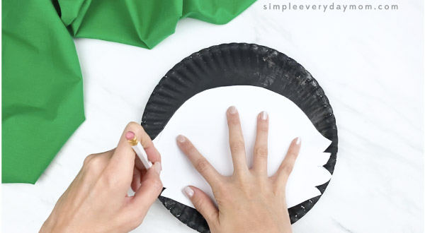 hands tracing skunk template onto paper plate