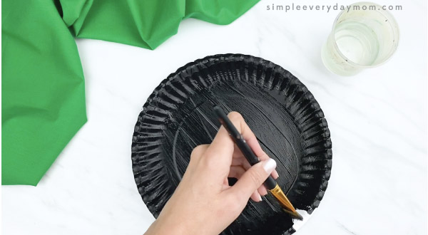 hands painting paper plate black