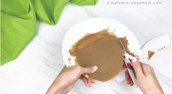 hands cutting out center circle of brown paper plat e