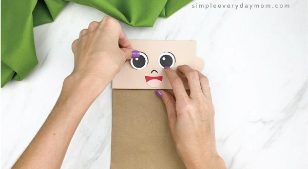 hands gluing eyes to paper bag pilgrim craft