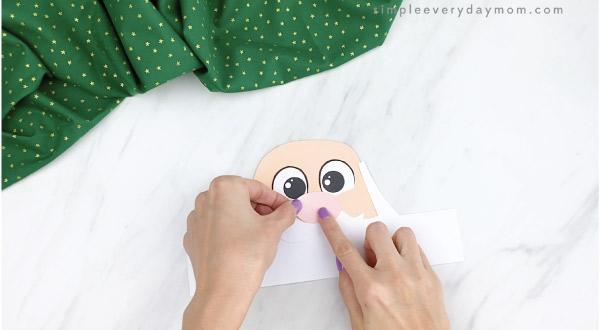 hands gluing nose onto Santa headband craft