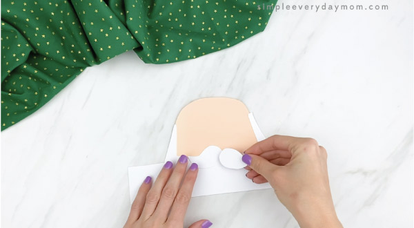 hands gluing mustache onto Santa headband craft