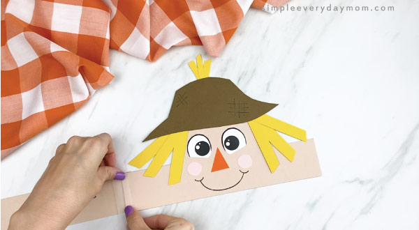 hands taping headband extenders to paper scarecrow headband craft