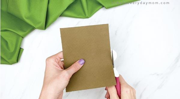 hands cutting cream paper off