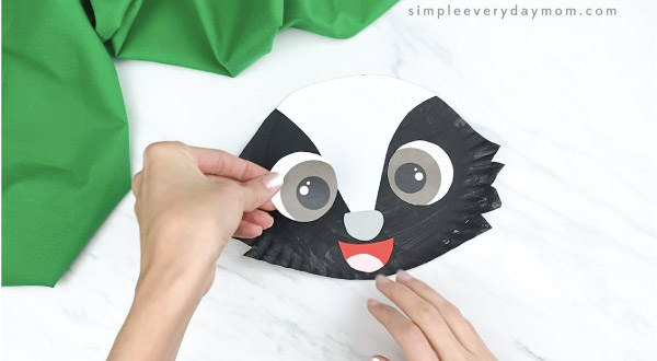 hands gluing eyes onto paper plate skunk craft