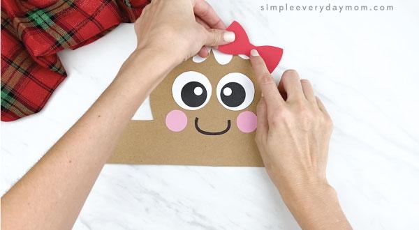 hands gluing hair bow onto gingerbread headband craft